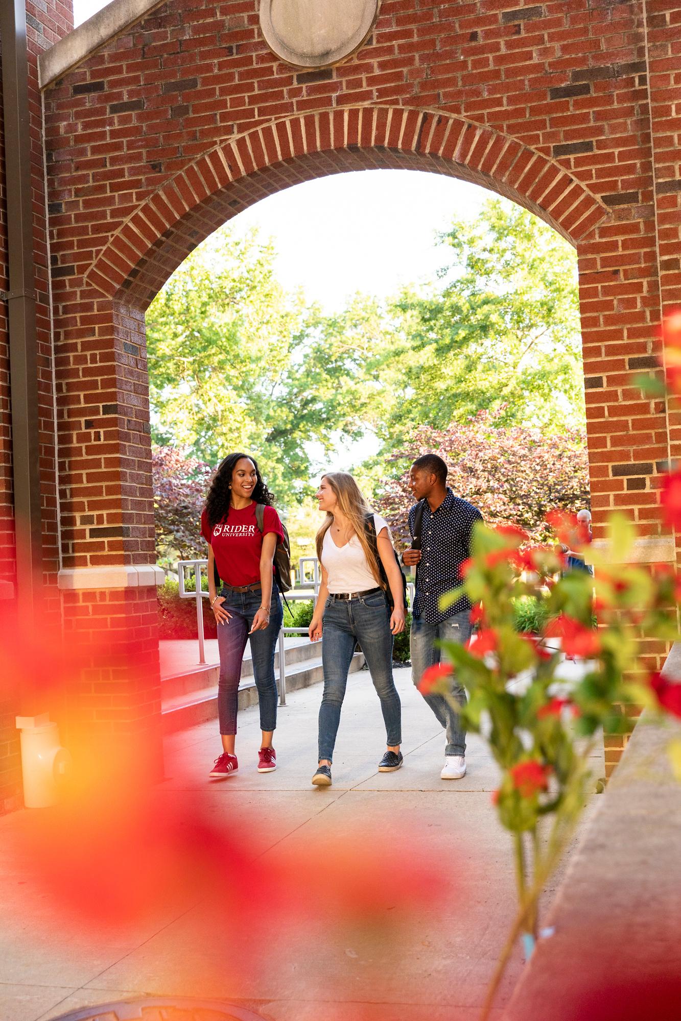Students walk under archway on Rider campus