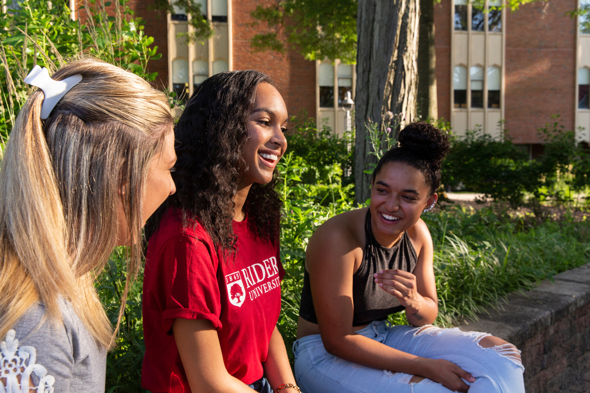 Three students talk and laugh together
