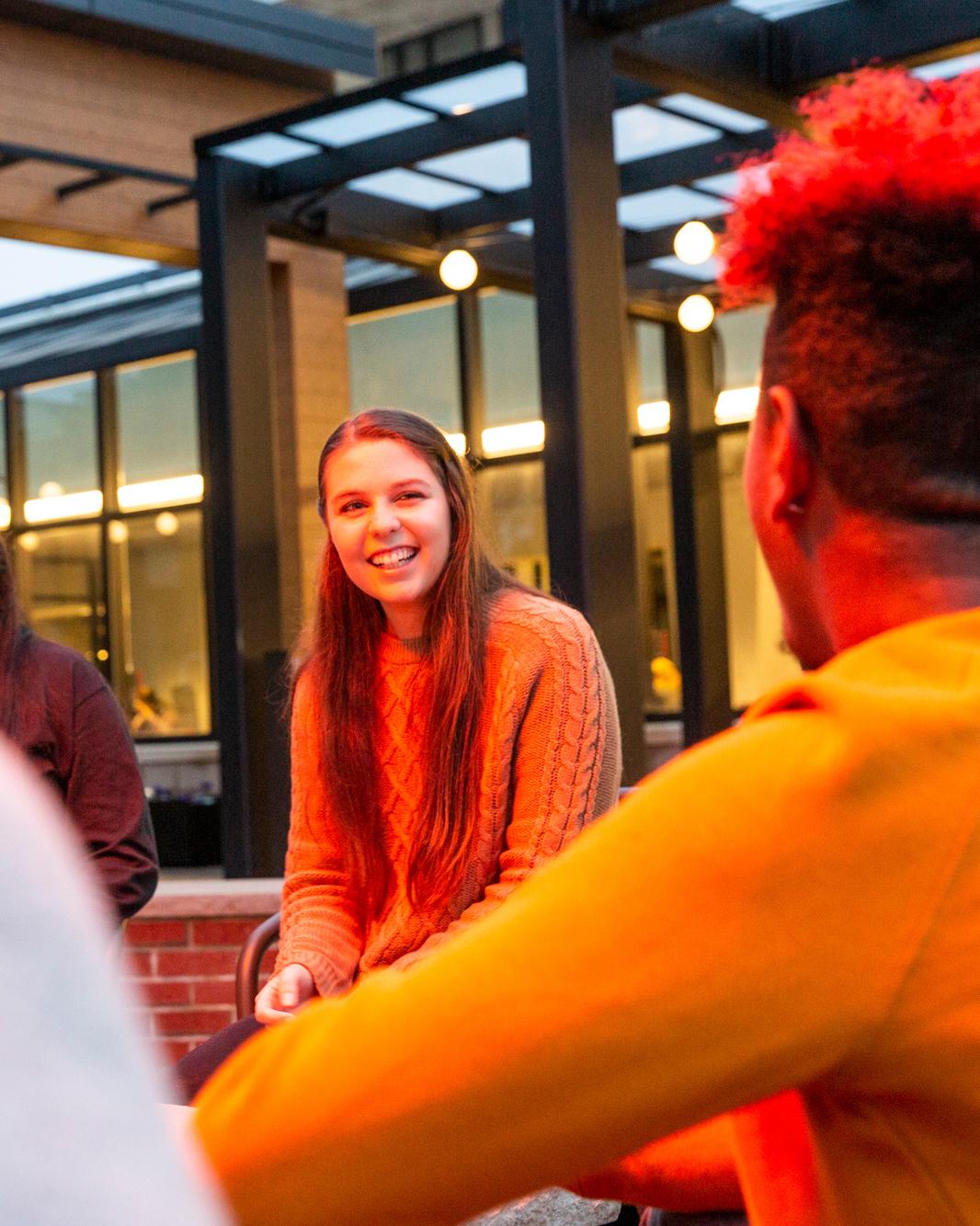 Students talk near fire pit