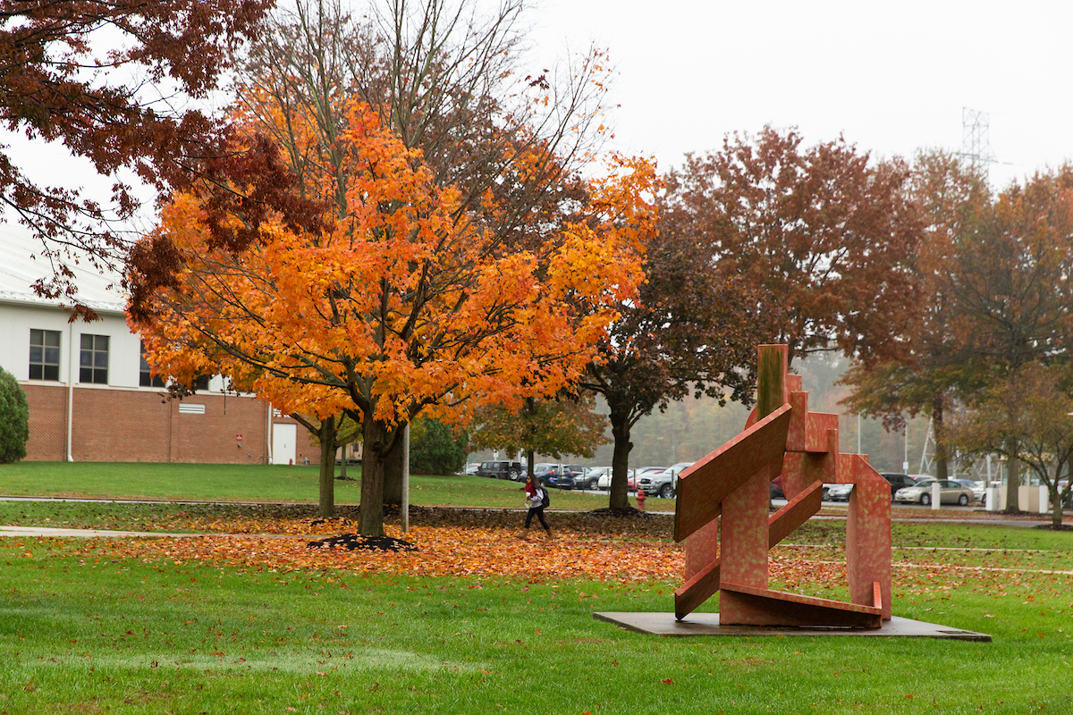 Student walks across campus in the fall.