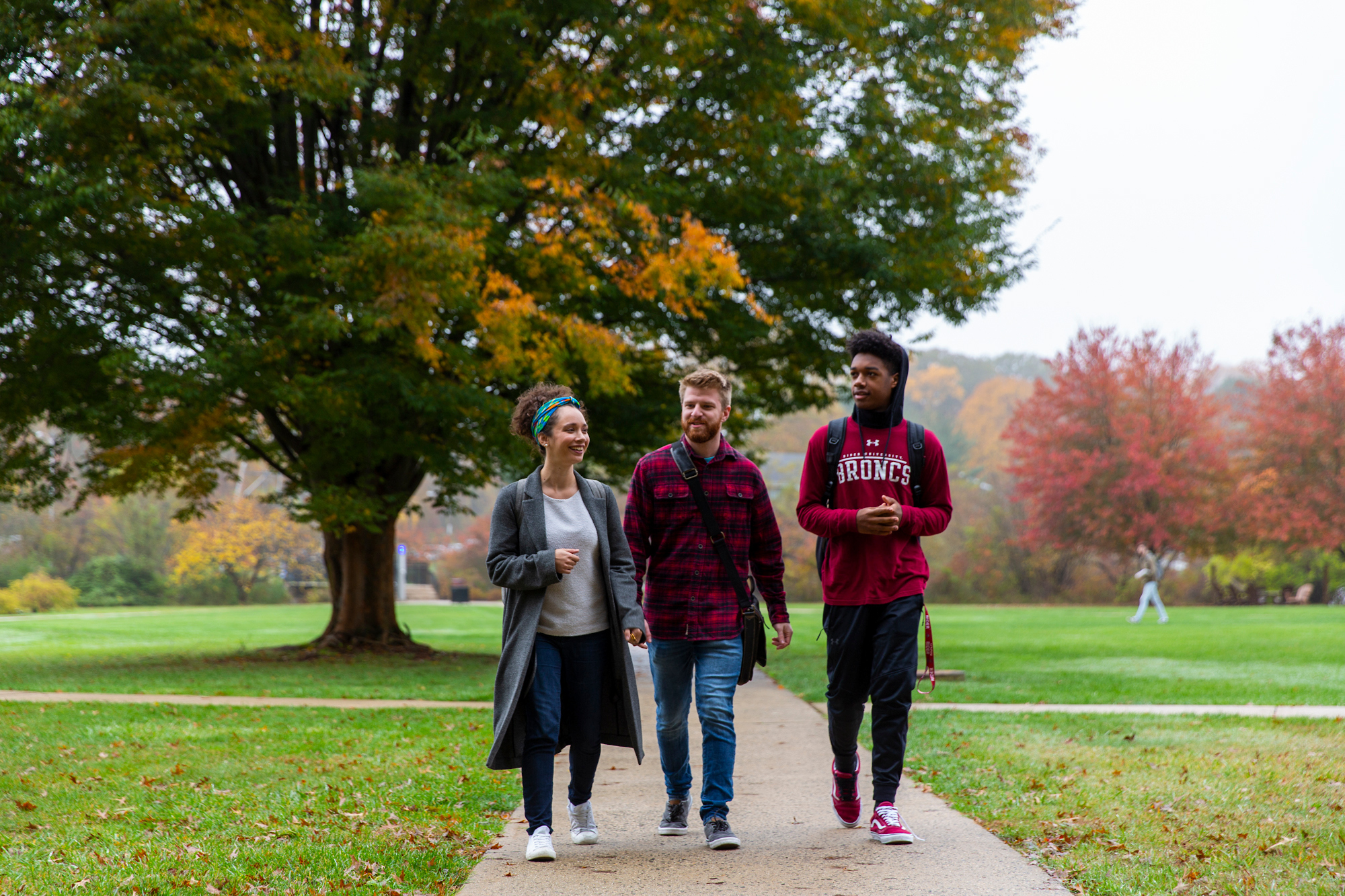 Three students walk to class in autumn
