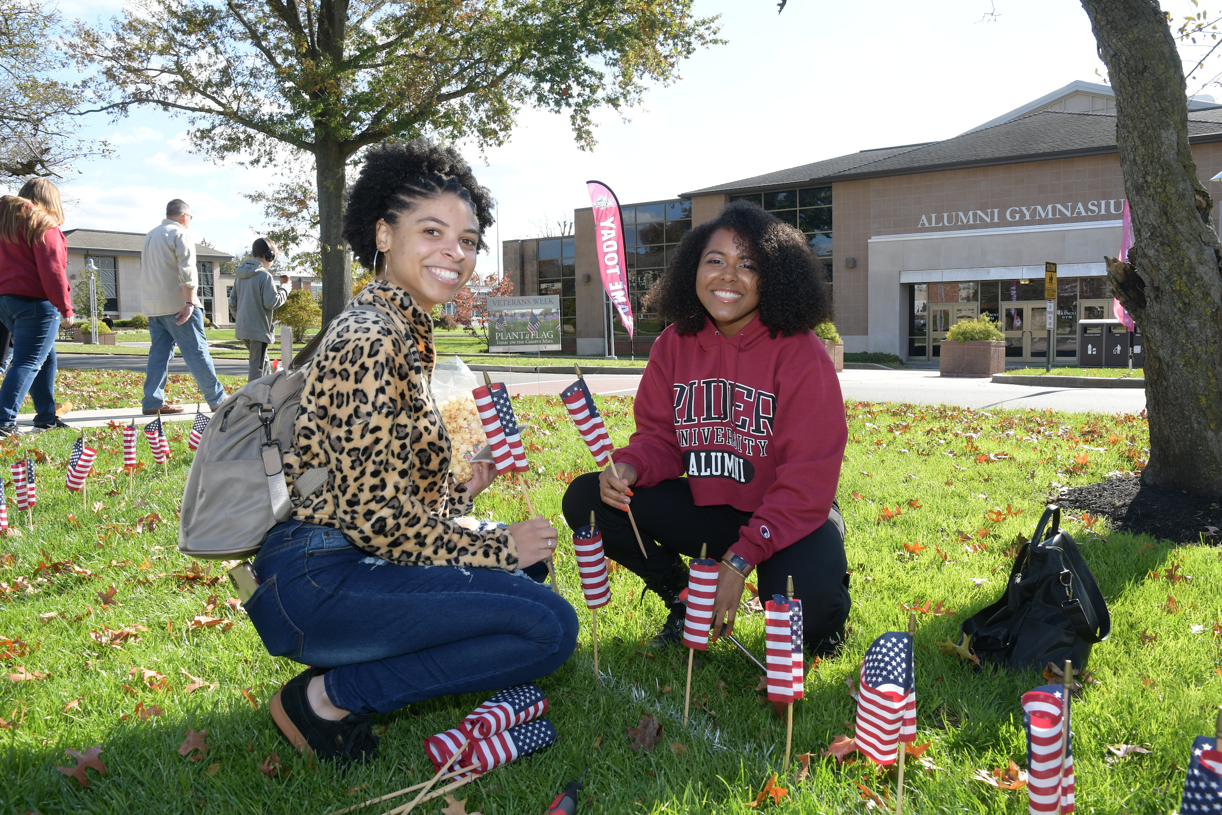 Alumni plant flags during Family Weekend