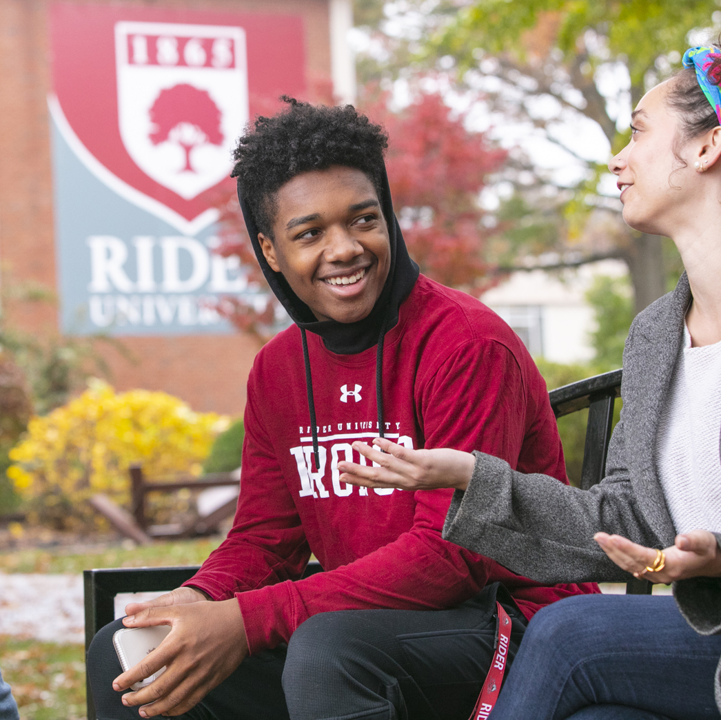 Students sit outside on campus