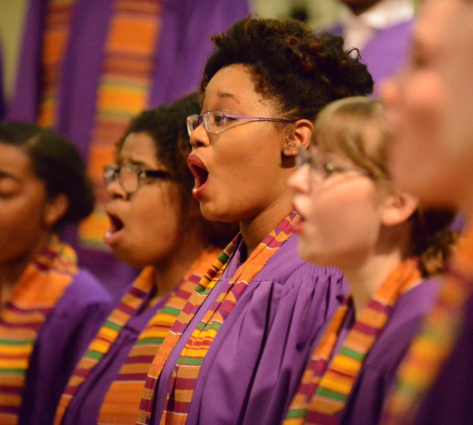 Group of female choral students dressed in vibrant colored robes