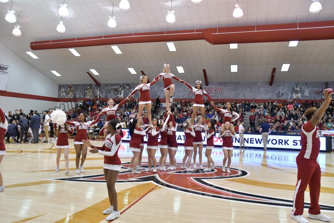 Cheerleaders cheer at basketball game.