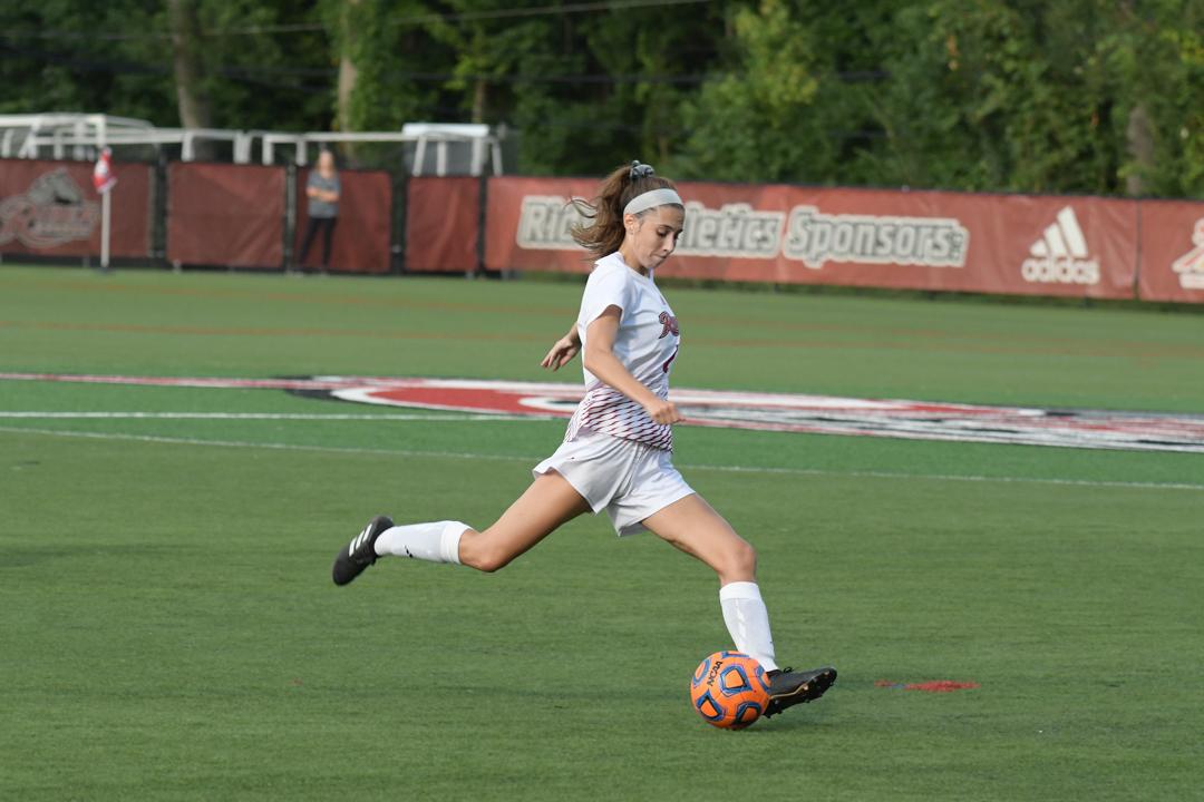 Soccer player kicks ball.