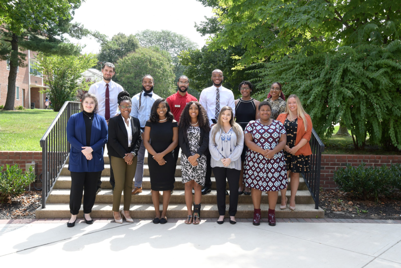 Graduate Assistants pose for photo on steps.