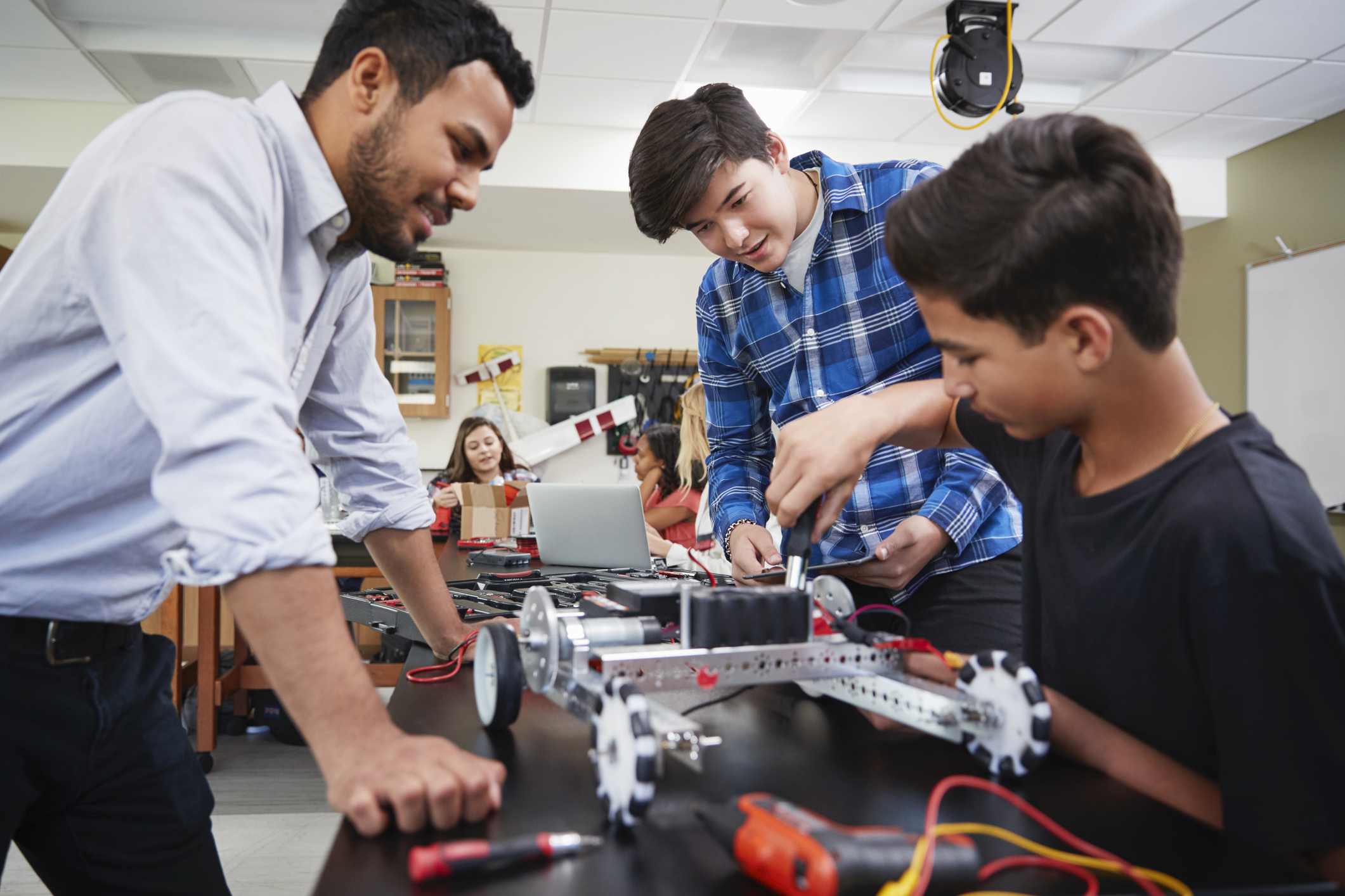 Teacher builds robot with students.