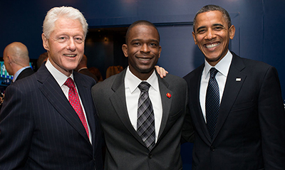 Image of Gregory Lorjuste with Bill Clinton and President Obama