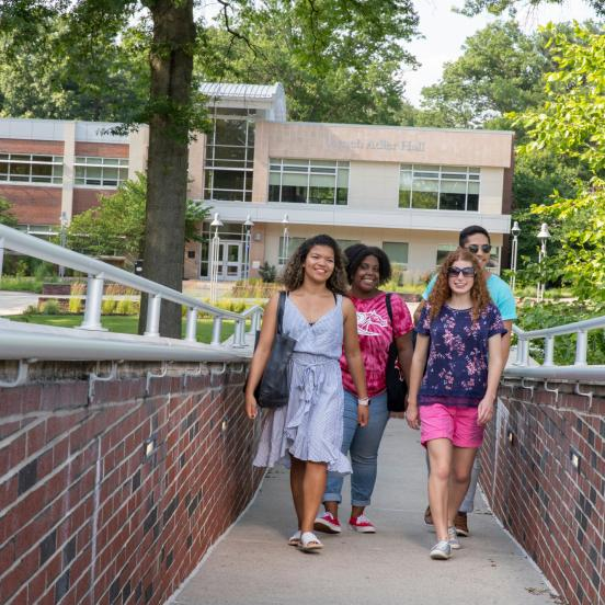 Four students walk across campus