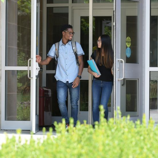Two students exiting Lynch Adler Hall