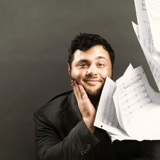 Alumnus poses for photo with sheet music.