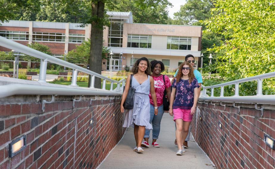 Four students walk to Moore Library