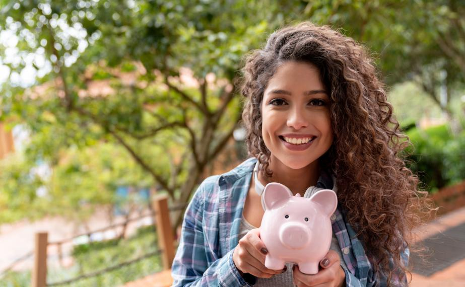 Smiling student holds piggy bank