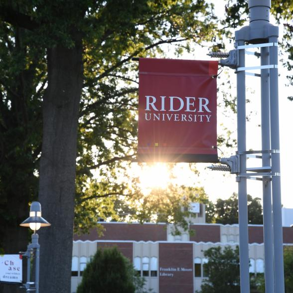 Rider sign at sunset in front of Moore library