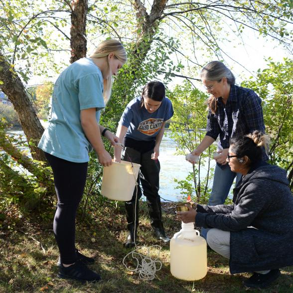 Group of students getting samples of water outdoors