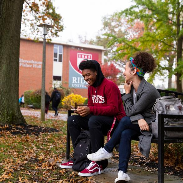 Students sit on bench talking on Rider campus.