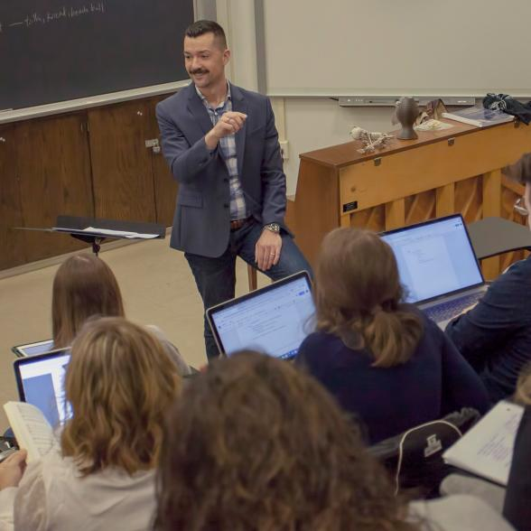Faculty next to a piano teaches a classroom of students