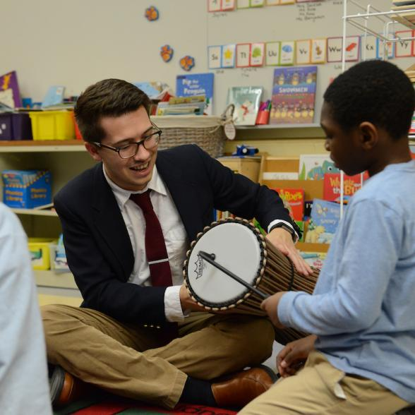 Male student works with children to play a drum