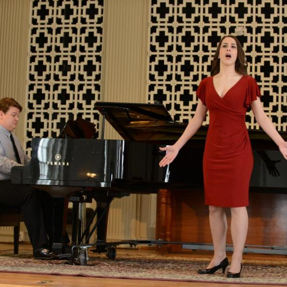 Female in red dress sings with the accompaniment of a pianist on a grand piano