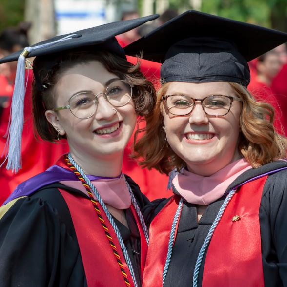 Two students pose for photos at Commencement