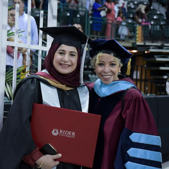 Student and staff member pose for photo at Commencement