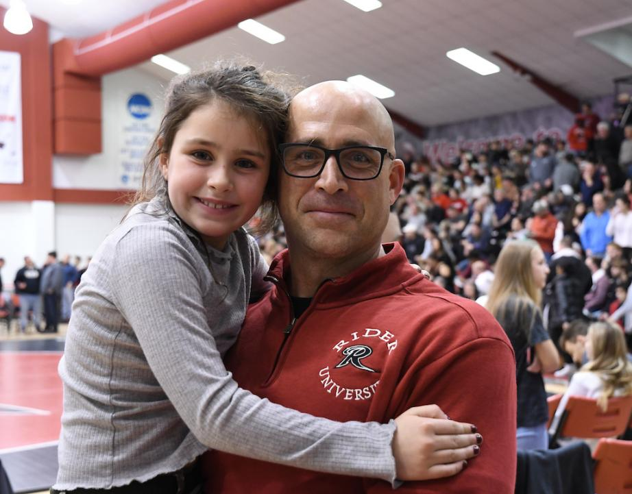 Rider Alumnus poses with daughter at Rider wrestling event.