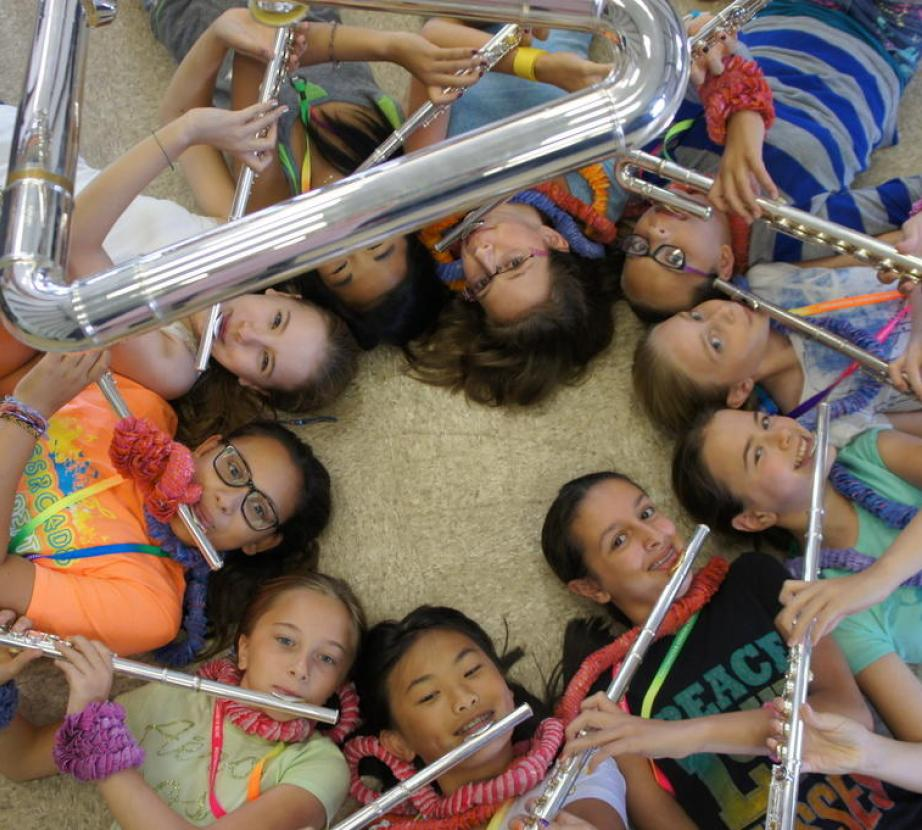 Circle of children playing flutes looking up