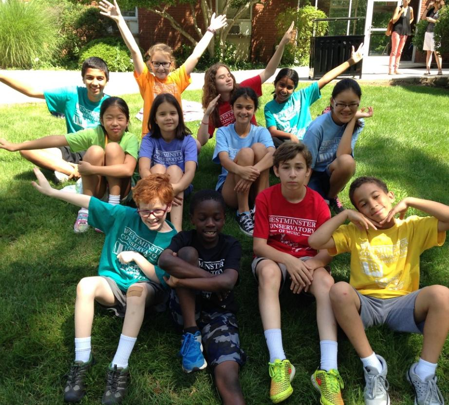 Pre-teen summer camp children posing with arms up