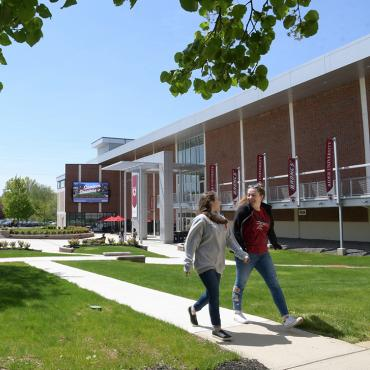 Students walk in front of Bart Luedeke Center