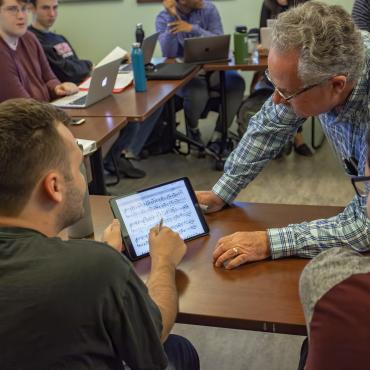 Male faculty member helps student on ipad