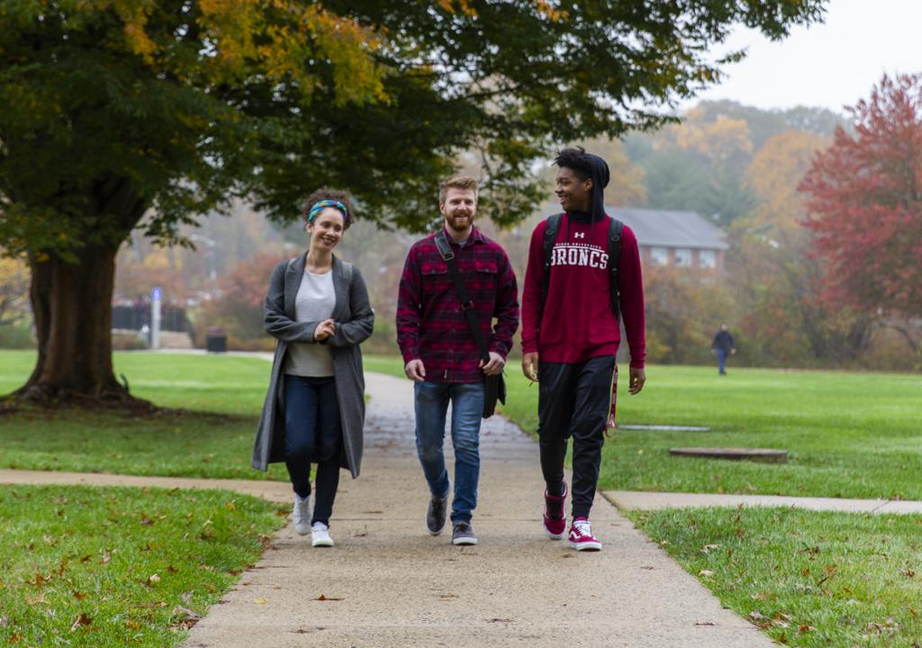 Three students walk on path in autumn